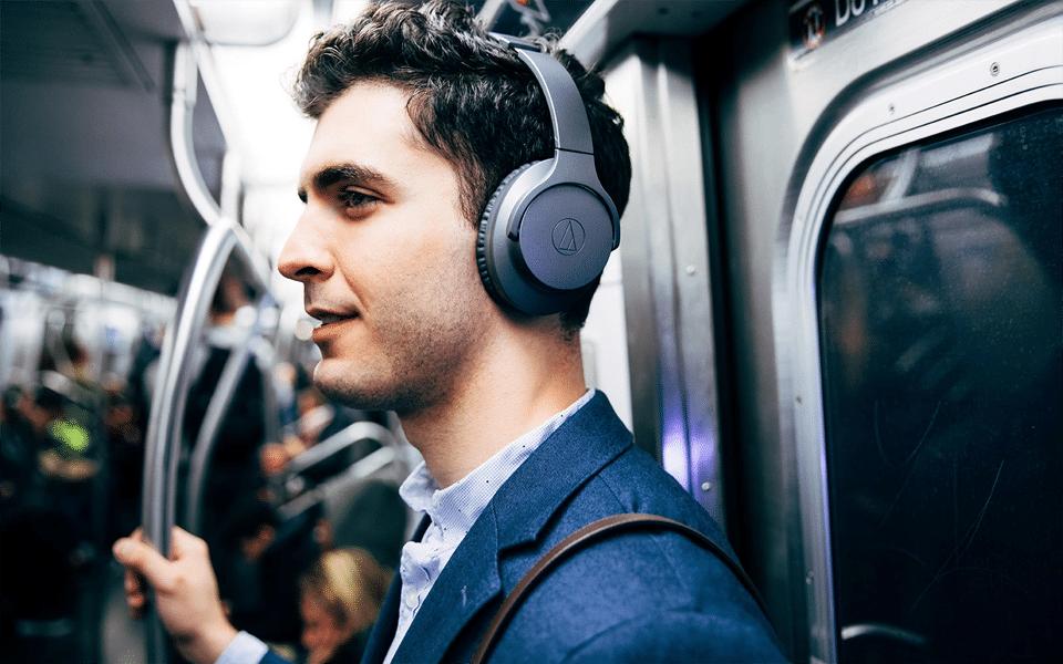Bărbat ascultând muzică în căști în metrou.