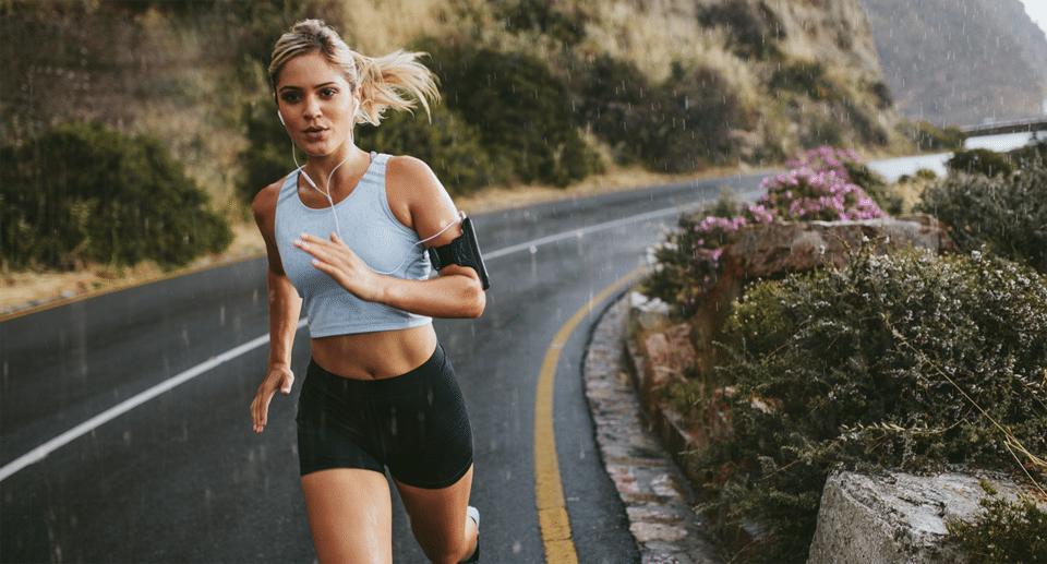 Fată blondă cu căști în ureche alergând prin ploaie.