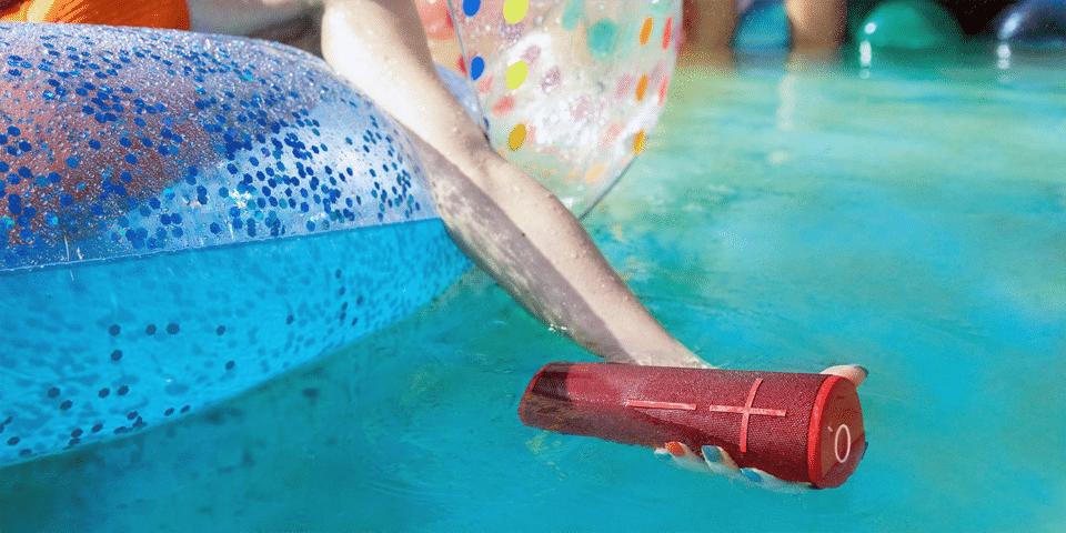 Fată ținând în apă o boxă bluetooth roșie.