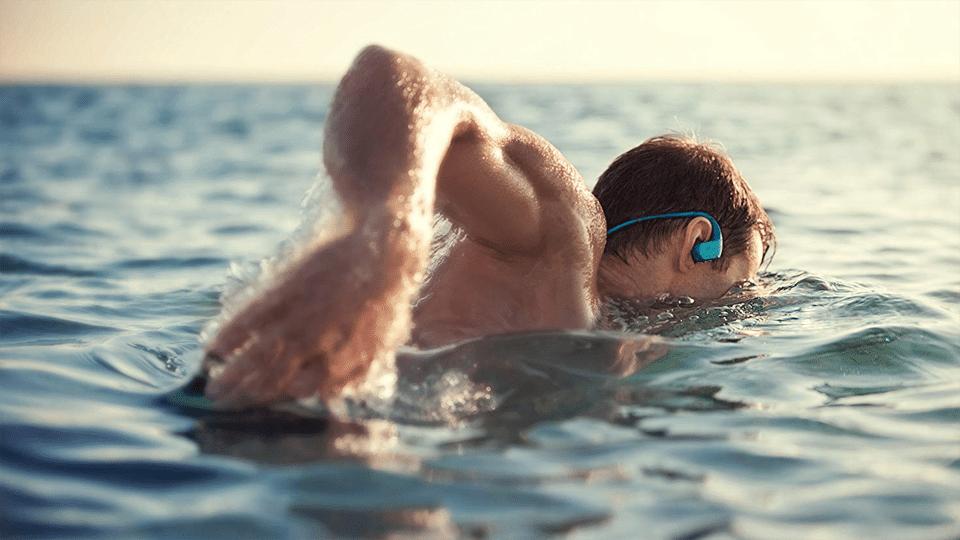 Bărbat cu căști pe urechi înotând.