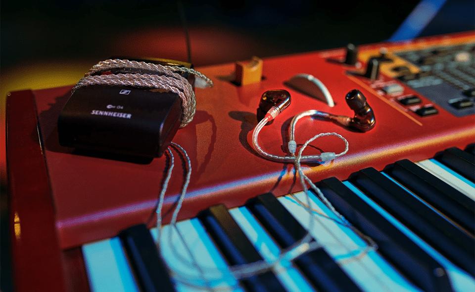 Căști legate la un amplificator Sennheiser pe o orgă muzicală roșie.