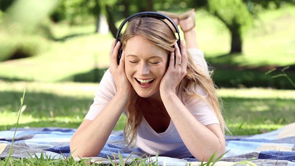 Fată stând pe o pătură pe iarbă și ascultând la căști.