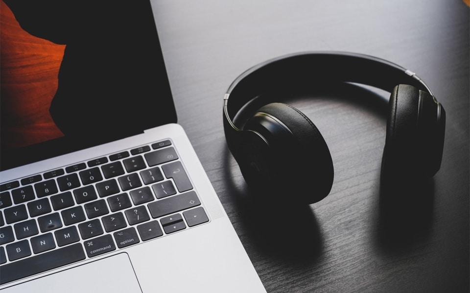 Casti over-ear langa un laptop.