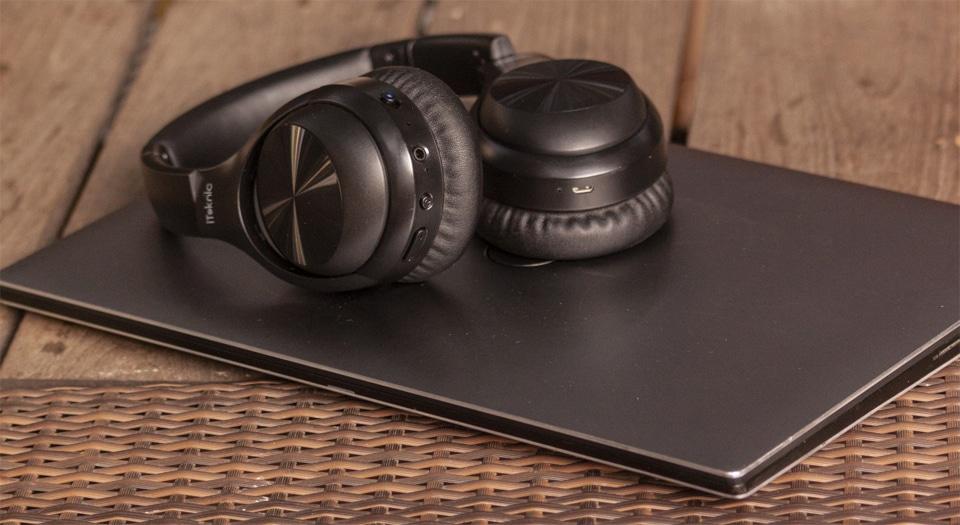 Casti iTeknic IK-BH002 asezate pe un laptop.