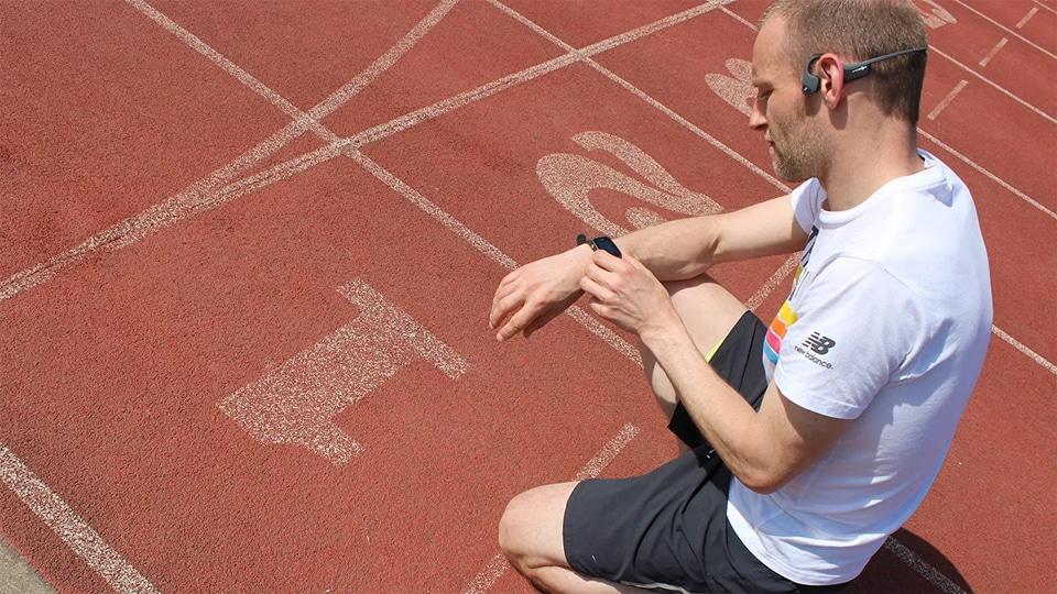 Barbat cu casti pe urechi stand pe o pista de atletism.