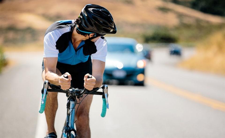 Ciclist cu casti pe urechi uitandu-se in spate la o masina.